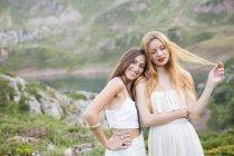 Ritratto di fidanzate sorridenti abbracciate dal lago di montagna — Foto stock