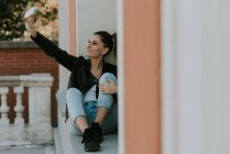 Porträt eines Mädchens beim Selfie auf der Fensterbank — Stockfoto