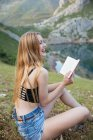 Laughing woman with long hair holding book while sitting on grass near mountain lake — Stock Photo