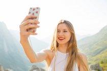 Portrait de femme aux longs cheveux blonds faisant selfie avec smartphone sur fond de montagnes — Photo de stock