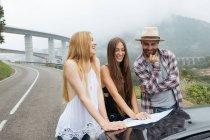 Due ragazze e l'uomo guardando nella mappa sulla strada — Foto stock