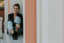 Jeune fille assise sur le rebord de la fenêtre et regarder la caméra — Photo de stock