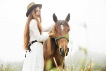 Side view of young brunette in white dress hugs brown horse in field — Stock Photo