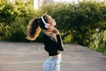 Content girl listening to music outside — Stock Photo