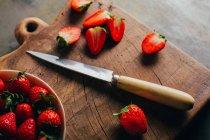 Fresas de corte en el tablero de corte - foto de stock