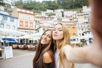 Zwei Mädchen lächeln in die Kamera, während sie ein Selfie mit der Altstadt machen — Stockfoto
