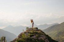 Vue latérale d'une femme posant contre du paysage des montagnes et des nuages dans le ciel — Photo de stock