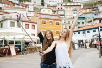 Two girls taking selfie with selfie-stick at city square over building facades — Stock Photo