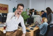 Porträt eines lächelnden Mannes, der am Tisch sitzt und im Hintergrund mit Büroangestellten telefoniert — Stockfoto