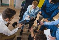 Hochwinkel-Ansicht multiethnischer Geschäftsleute mit Smartphones bei Treffen im Büro — Stockfoto
