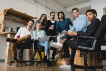 Low angle view of smiling office workers sitting in open-space and looking at camera. — Stock Photo