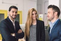 Портрет жизнерадостных деловых людей, позирующих в современном офисе — стоковое фото