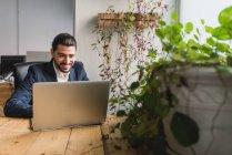 Ritratto dell'uomo d'affari che si siede al tavolo e usando il portatile sul posto di lavoro di ufficio — Foto stock