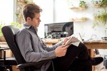 Jeune homme d'affaires, lisant le journal tout en étant assis dans la chaise de bureau — Photo de stock