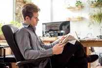 Young businessman reading newspaper while sitting in office chair. — Stock Photo