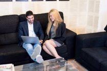 Smiling business people sitting on couch and looking at laptop — Stock Photo