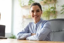 Smiling businesswoman at workplace in office looking at camera — Stock Photo