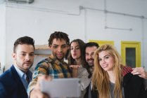 Portrait of group of business people taking selfie with smartphone camera in office. — стокове фото