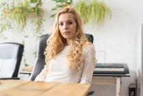Nachdenkliche blonde Geschäftsfrau sitzt am Arbeitsplatz und blickt in die Kamera — Stockfoto