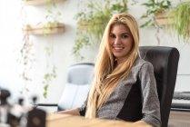Sorridente ragazza bionda seduta sul posto di lavoro e guardando la fotocamera — Foto stock