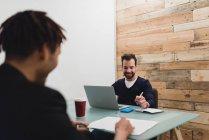 Портрет улыбаясь бизнесменов, сидя за столом с ноутбуком и документы в офисе — стоковое фото