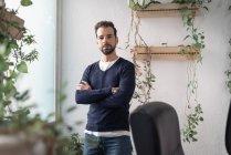 Портрет бизнесмена, стоящего у окна и смотрящего в камеру — стоковое фото