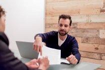 Dos hombres de negocios firmando papeles en la oficina - foto de stock