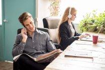 Человек, говоря телефон и глядя на газеты во время женщина, работающая на ноутбук — стоковое фото
