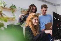 Porträt von blonde Mädchen zeigen Kollegen am pc-Bildschirm im Büro. — Stockfoto