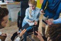 Erhöhte Ansicht von Büroangestellten in Smartphones während der täglichen Besprechung im Büro suchen — Stockfoto