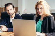 Человек, глядя на камеру во время женщина коллега просмотра ноутбук на рабочем месте — стоковое фото