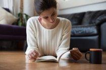 Портрет брюнетки, лежащей на полу и читающей книгу  . — стоковое фото