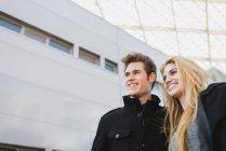 Низкий угол портрет пара, выйдя из офисного здания — стоковое фото