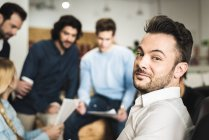 Smiling man looking at camera during brainstorm meeting at office — Stock Photo