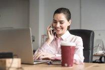 Alegre morena empresaria hablando por teléfono en el lugar de trabajo - foto de stock