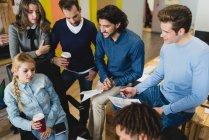 Vista de ángulo alto de la gente de negocios multiétnicos comunicándose mientras se reúnen - foto de stock