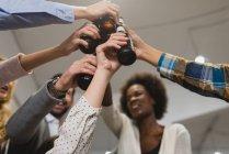 Vista de ángulo bajo de los colegas golpeando botellas en la oficina mientras hacen equipo - foto de stock