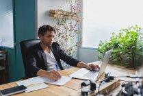 Ritratto di uomo d'affari che usa il computer portatile e scrive su carta sul posto di lavoro — Foto stock