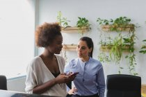 Portrait of businesswomen talking at open space office — Stock Photo