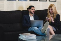 Portrait of colleagues sitting at couch in office and browsing devices — Stock Photo