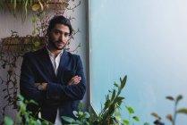 Портрет бизнесмена, стоящего у окна со скрещенными руками и смотрящего в камеру — стоковое фото