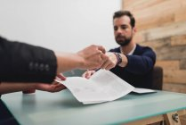 Crop hand of giving a pen to business partner to sign papers — Stock Photo