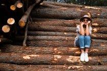 Tendance femme posant sur les bûches de bois — Photo de stock