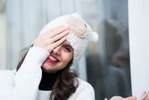 Portrait of smiling woman wearing knitted hat closing one eye with hand and looking at camera — Stock Photo