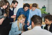 Equipe de escritório na reunião diária de pé e olhando para baixo na mesa — Fotografia de Stock