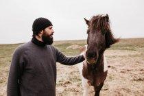 Человек гладит дикую дикую лошадь — стоковое фото