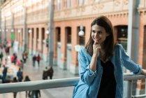Femme gaie debout près de la main courante — Photo de stock