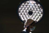 Lampada sopra chirurgo femminile durante l'operazione — Foto stock