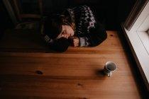 Жінка, лежачи на стіл з кухля — стокове фото