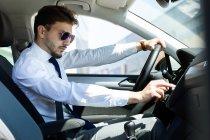 Mann benutzt Navigationsgerät im Auto — Stockfoto